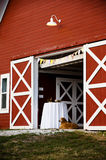 Dog and barn. A dog sitting at the entrance to a red barn Stock Photos