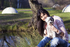 Dog being groomed with hair brush by young woman in the park. Woman sitting in a park  and  grooming a dog purebreed maltese Royalty Free Stock Photos