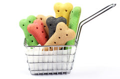 Dog biscuits in a metal basket. Colored dog bones stacked inside a frying basket on a white background Stock Image