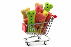 Dog biscuits in a shopping trolley. Colored dog biscuits in a supermarket shopping trolley stock photo