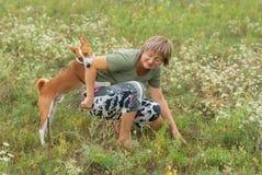 Dog bites master while playing outdoors Stock Photography