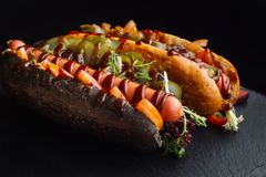 Although the dog in a black bun, with pickled cucumbers. Stock Image