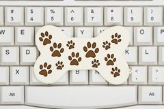 A dog bone with paw prints on a keyboard. Getting pet supplies on the Internet, A close-up of a keyboard with a wood dog bone and paw prints royalty free stock photo