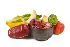 Dog bowl filled with biologically appropriate raw food containing meat chunks, fruits and vegetables