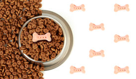Dog bowl with pet feed on the half white background and scattered dry food. Dog bowl with pet feed on the half white background pink bones and scattered dry food Stock Images