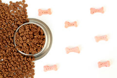 Dog bowl with pet feed on the half white background and scattered dry food. Dog bowl with pet feed on the half white background pink bones and scattered dry food Royalty Free Stock Photo