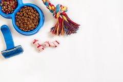 Dog care items, isolated on white background. Dry pet food in bowl, toy and bones. Top view Royalty Free Stock Photography