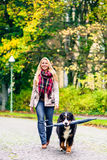 Dog carrying umbrella of his mom in autumn walk. Outdoors Royalty Free Stock Photo