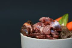 Dog or cat bowl filled with mixture of biologically appropriate raw food containing  meat, entrails and vegetables