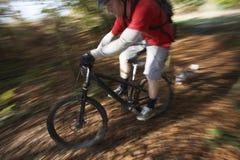 Dog Chasing Man On Mountain Bike Stock Image