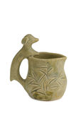 Dog creamer jug. A unique clay sculpted creamer or jug with a dog design as the handle and tradisional bamboo carvings on side Royalty Free Stock Photo