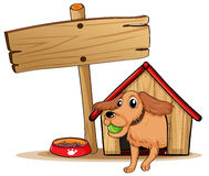 A dog with a doghouse beside an empty signage Stock Image