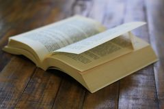 Dog eared paperback book on worn wooden surface royalty free stock photography