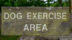 A dog exercise area sign. A wooden dog exercise area sign with white letters Stock Photos