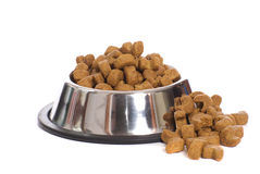 Dog Food. Over flowing from a metal dog bowl, isolated against a white background Royalty Free Stock Images