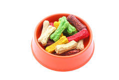 Dog food. A plastic bowl filled with colorful pet food in biscuit bone shapes. Image isolated on white studio background Royalty Free Stock Images