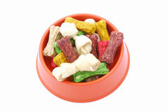 Dog food in bowl. A big plastic bowl of colorful little dog treat bones. Image isolated on white studio background Stock Photography