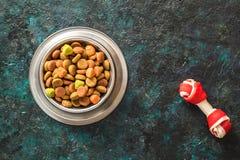 Dog food in metallic bowl on black dark blue background royalty free stock photo