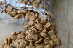 Dog food pour from plastic bag Royalty Free Stock Photos