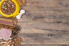 Dog food selection on wooden background Stock Photos