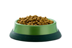 Dog food on white background. Dog food heaped in green plastic bowl on white background Royalty Free Stock Photo