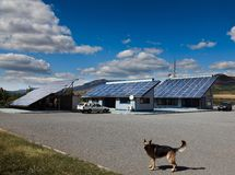Dog in front of a house with photovoltaic Stock Image