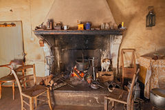 A dog gets hot inside the fireplace. Interior of an old country house where a dog gets hot inside the fireplace stock photo
