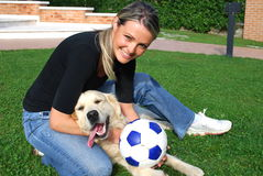 Dog and girl play togheter. In the garden with the ball Royalty Free Stock Photos