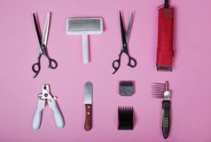 Dog grooming tools and accessories set on pink background. pet care and hygienic concept, flat lay. Scissors, coat clipper, brush, Nail Clipper, thinning stock images