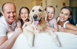 Dog and happy family. Pet surrounded by family of four sitting on sofa Royalty Free Stock Photography