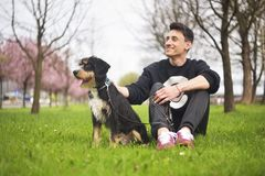 Dog and his owner - Cool dog and young man having fun in a park - Concepts of friendship, pets, togetherness.Man with his dog play Stock Photo