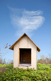 Dog house. A dog house outside in a green grassy area with a blue sky and cloud
