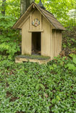 Dog house. This one was used to shelter most of our cat because our old dog died shortly after the construction of this one. At the foot of it a carpet of Royalty Free Stock Photography