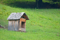 Dog house. A small wooden dog house near the fir tree Royalty Free Stock Images