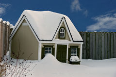 Dog house in snow. A beautiful dog house near a wooden fence on a winter day.   Snow accumulated on the ground, top of the fence and the roof of the house Royalty Free Stock Photo