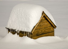 Dog house in snow bank Stock Photo