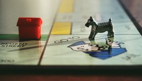 Dog and House Toy on Monopoly Board Game royalty free stock photo