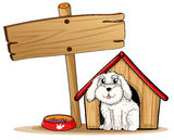 A dog inside the dog house with a wooden signboard Royalty Free Stock Photos