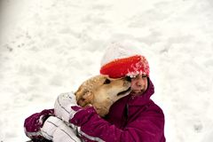The dog jumps for joy at the girl and licks her face. The girl is playing with the dog in the snow and gives him a kiss stock photo
