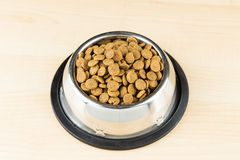 Dog Kibbles in a bowl on wooden floor Stock Image