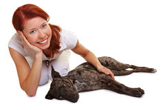 Dog laying beside happy woman Stock Photography