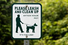 Dog leash and scoop sign with green tree stock photos