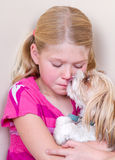 Dog licking childs face. Sad child sitting in corner with dog licking her face trying to comfort her stock image