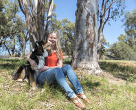Dog Licking Woman Sitting in Park Royalty Free Stock Photos