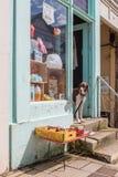 Dog looks out of shop door. LYME REGIS, UK - APRIL 11, 2016: Dog looks out of tourist shop door onto the high street stock photo