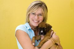 Dog Lover. Beautiful woman holding a puppy royalty free stock photo