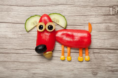 Dog made of red pepper. On wooden background stock photos