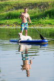 The dog and the man float by the boat on the lake. Stock Images
