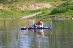 The dog and the man float by the boat on the lake. Royalty Free Stock Images