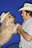 Dog and man wearing cowboy hats. Royalty Free Stock Images